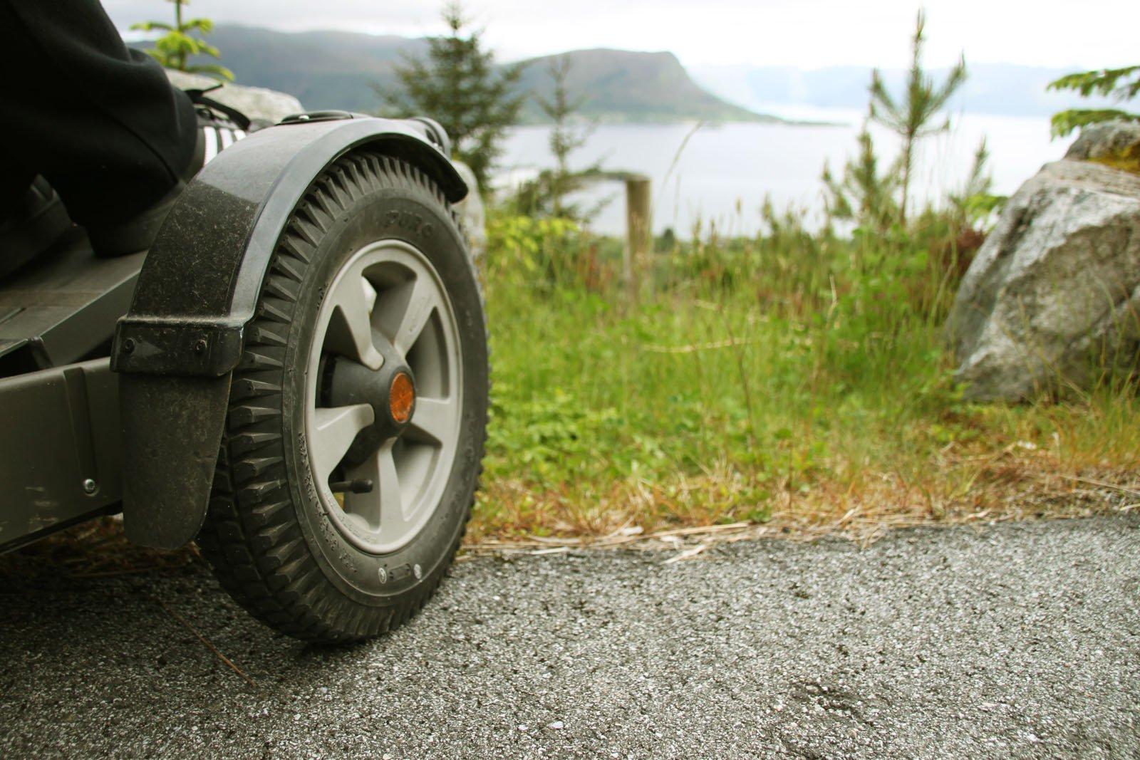 Bilde av hjulet til et assistansekjøretøy som står parkert på gress med utsikt over sjøen.