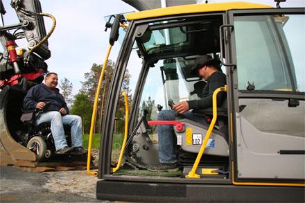Bilde av en gravmaskin med en mann i førersetet og en annen mann i rullestol som er parkert i skuffa.