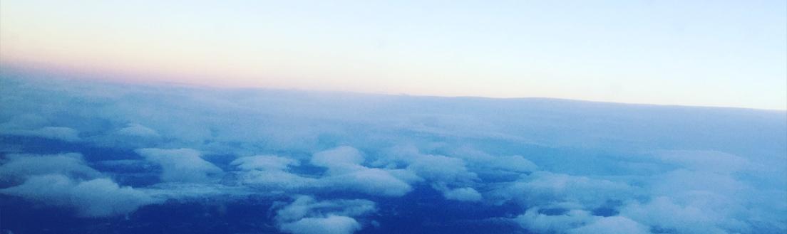 Bilde av en skyfull himmel tatt fra vinduet til et fly.