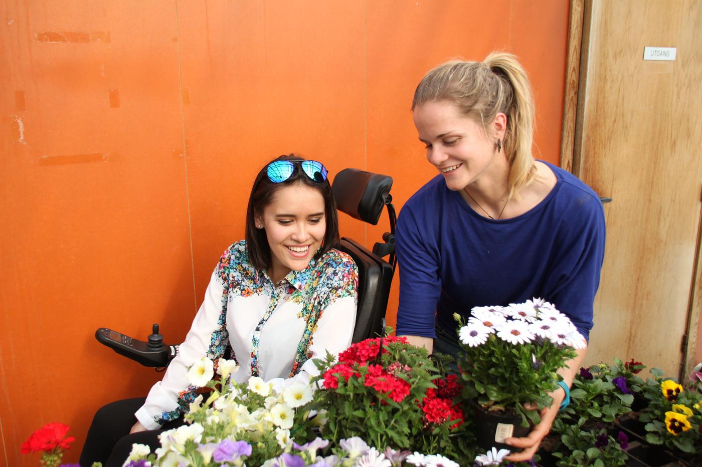 Bilde av en kvinne i rullestol som kikker på blomster. En annen kvinner viser fram ulike blomster i hvitt, rødt, gult og lilla.