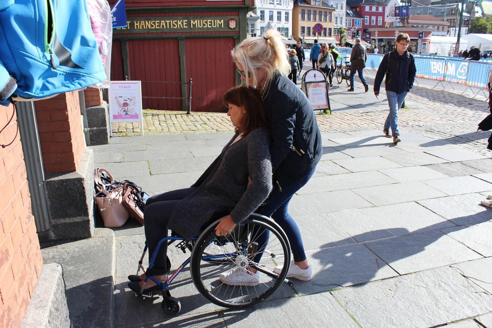 Bilde av Bergens varaordfører Marita Moltu i rullestol som får assistanse inn i en bygning av en assistent fra Prima Assistanse.