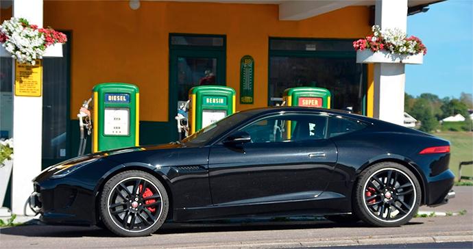 Bilde av en svart sportsbil. Den står parkert foran en landlig bensinstasjon med gammeldagse pumper. I bakgrunnen skimtes en søyle til høye og en til venstre, begge med blomsterkasser.